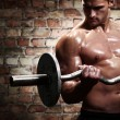 Muscular guy doing exercises with barbell — Foto Stock