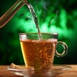 Hot green tea in glass teapot and cup — Stock Photo