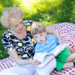 Senior woman reading book to her grandson — Stock Photo