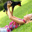Happy woman lying on the grass with her dog — Stock Photo