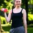 Royalty-Free Stock Photo: Woman working out with dumbbells in the park
