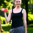 Woman working out with dumbbells in the park — Stock Photo #12792450