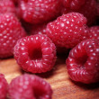 Fresh raspberries on wooden surface — Stock Photo #12792660