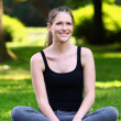 Fitness girl relaxing after workout in the park — Stock Photo