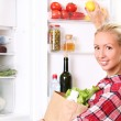 Young woman is putting a food into the fridge — Foto Stock
