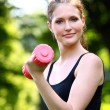 Beautiful woman with pink dumbbell in the park — Stock Photo