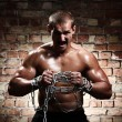 Muscular man with chains on his wrists — Stock Photo #12793042