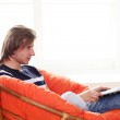 Happy handsome guy relaxing with laptop — Stock Photo