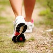 Stock Photo: Female legs jogging on a trail