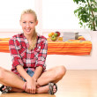 Happy woman sitting on the floor — Stock Photo