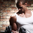 Muscular guy doing exercises with dumbbell — Stok fotoğraf