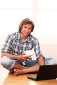 Handsome guy with a cup of coffee and laptop — Stock Photo