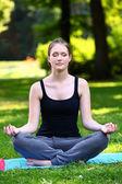 Beautiful woman relaxing in yoga pose — Stock Photo