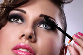 Beautiful woman face with mascara brush — Stock Photo