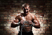 Muscular man with chains on his wrists — Stock Photo