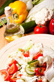Wooden plate with vegetable salad — Stock Photo