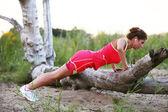 Woman doing push ups on the broken tree — Stockfoto