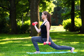 Young woman doing lunges with dumbbells — Photo