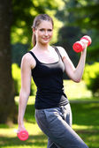 Woman working out with dumbbells in the park — Stock Photo
