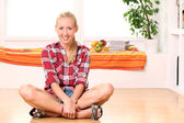 Happy woman sitting on the floor — Stock Photo