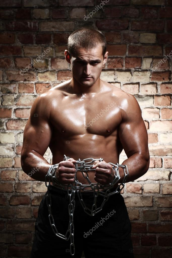 Muscular man with chains on his wrists against brick wall — Stock Photo #12793325