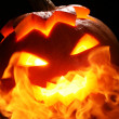 Halloween pumpkin in fire - Stock Photo