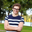 Portrait of young cute man with glasses in park — Stock Photo