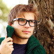 Handsome guy at cold autumn day in the park — Stock Photo
