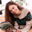 Stock Photo: Cute young woman reading magazine at home