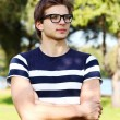 Portrait of young cute man with glasses in park — Stock Photo #14674673
