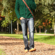 Handsome guy walking with cellphone in park — Stock Photo