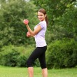 Woman doing exercises with dumbbells in the park - Stock Photo