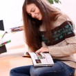 Cute young woman reading magazine at home — Stockfoto