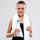 Smiling girl with towel and bottle of water — Stock Photo