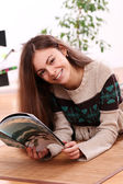 Cute young woman reading magazine at home — Stock Photo