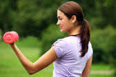 Woman doing exercises with dumbbells in the park — Stock Photo