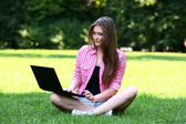 Beautiful woman with laptop in park — Stock Photo