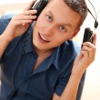 Young man listening music at home - Stock fotografie