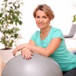 Cute and smiling middle aged woman with abs ball — Stock Photo #15505733