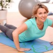 Slim mid aged woman do fitness exercises at home — Stock Photo