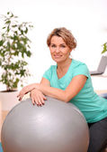 Cute and smiling middle aged woman with abs ball — Stock Photo