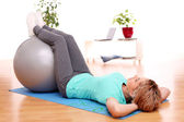 Slim mid aged woman do exercises with ball — Stock Photo