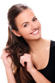 Attractive smiling woman touching her hair — Stock Photo