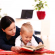 Mother with son reading a book at home — Stock Photo