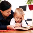 Mother with son reading a book at home - Stock Photo