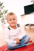 Little boy is sitting on a floor at home — Stock Photo