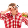 Funny man in glasses looking at hamburger — Stock Photo