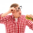 Funny man in glasses looking at hamburger - Stock Photo