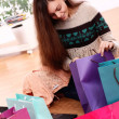 Attractive woman checking shopping bags at home — Stock Photo