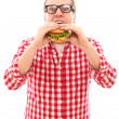 Funny man in glasses eating hamburger — Stock Photo #16688067